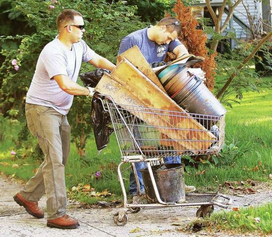 Alton police officers, in this 2017 file photo, clean up a property on East 8th Street as part of city efforts to help in-need residents with sorely-needed maintenance projects. Photo: John Badman | Telegraph File Photo