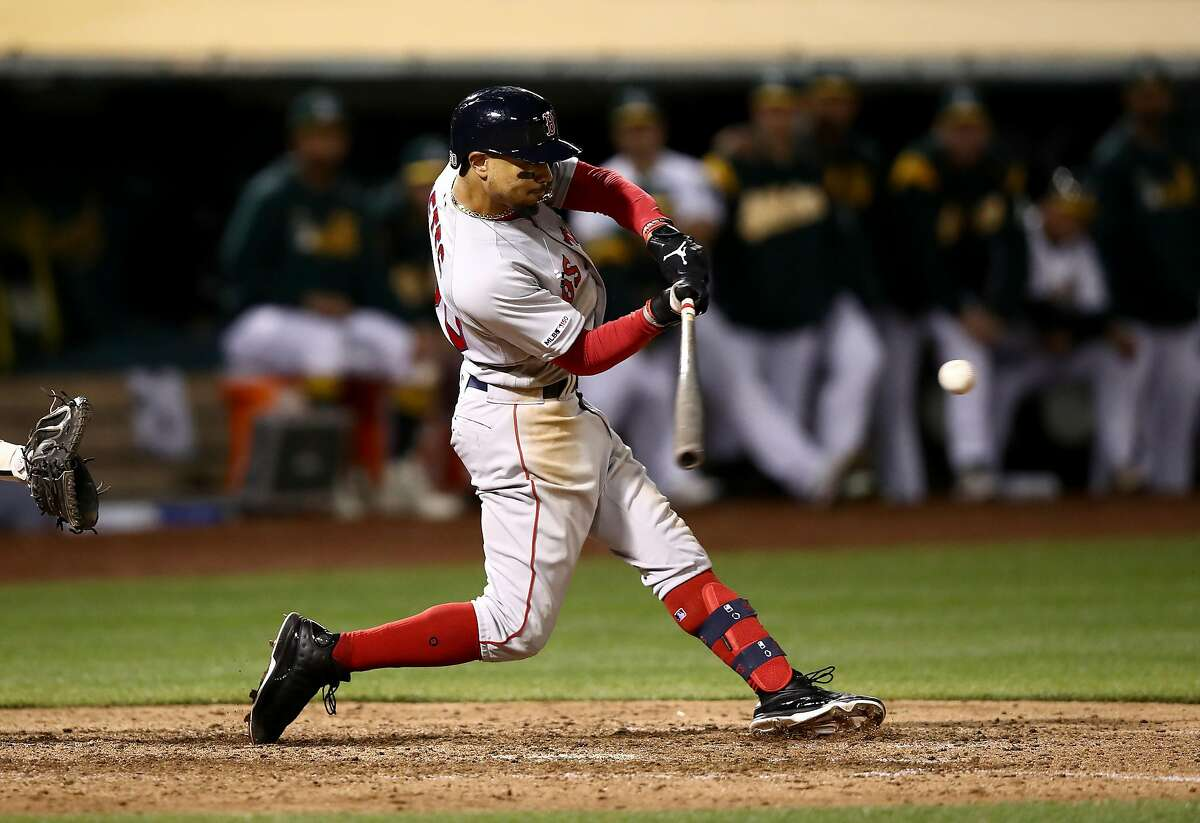 OAKLAND, CALIFORNIA - APRIL 03: Mookie Betts #50 of the Boston Red Sox hits a double that scored two runs in the ninth inning against the Oakland Athletics at Oakland-Alameda County Coliseum on April 03, 2019 in Oakland, California. (Photo by Ezra Shaw/Getty Images)