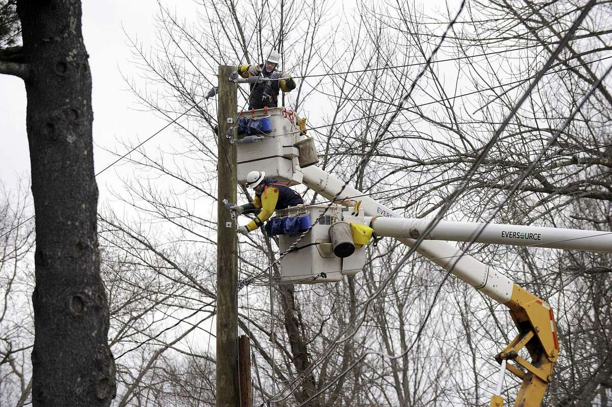 Eversource employees work to restore power at the intersection of Mountainville and Long Ridge Roads in Danbury Monday, March 5, 2018. The lines came down during a weekend storm.