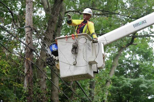 Workers with Eversource power company including Josh Goldin repair the electrical lines on Quarry Road Tuesday, October 9, 2018, after a tree limb came down on wires leaving resients in the area withour power in Norwalk, Conn.