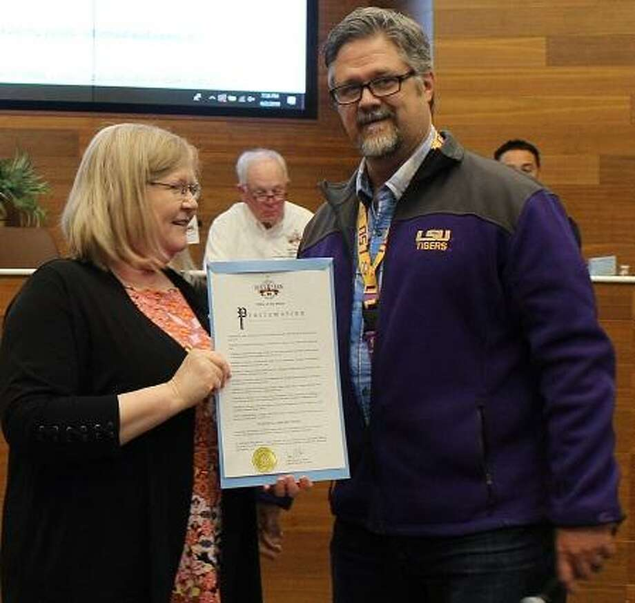 """After weeks of coping with the effects of the Intercontinental Terminals Co. disaster on his community, Deer Park Mayor Jerry Mouton, left, deals with more pleasant matters at the first council meeting since the fires, such as giving an award to Deer Park Library Director Rebecca Poole. If there are lessons we can learn from this,"""" he says of the ITC incident, """"I'm going to make sure we do, and we will get through this."""""""