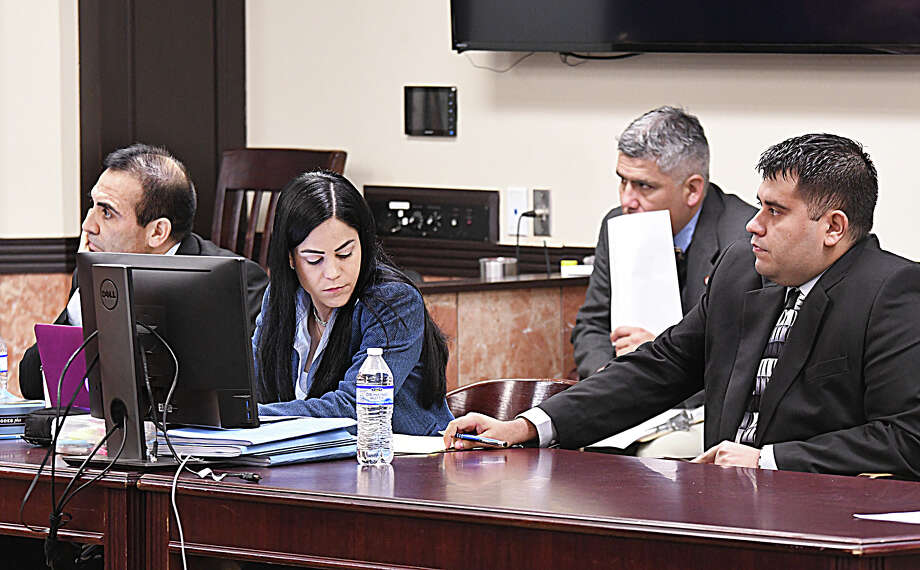 Edgar Mario Moreno, right, passes a note to his defense attorney Claudia Balli in his sexual assault trial in the 111th District Court, Tuesday, April 2, 2019. Also defending Moreno is attorney Roberto Balli, left. Photo: Cuate Santos, Laredo Morning Times / Laredo Morning Times