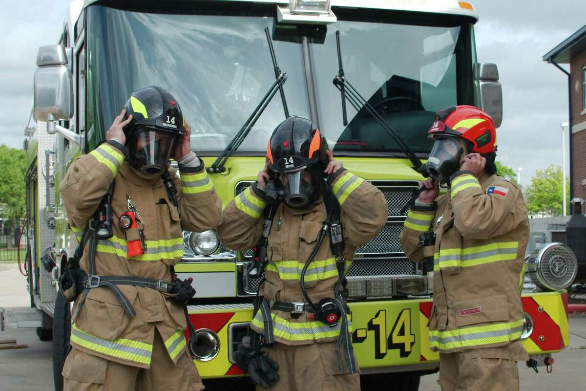 Webster firefighters Jason Crockom, Jeremy Falcone and Shane Martin strap on their new helmets.