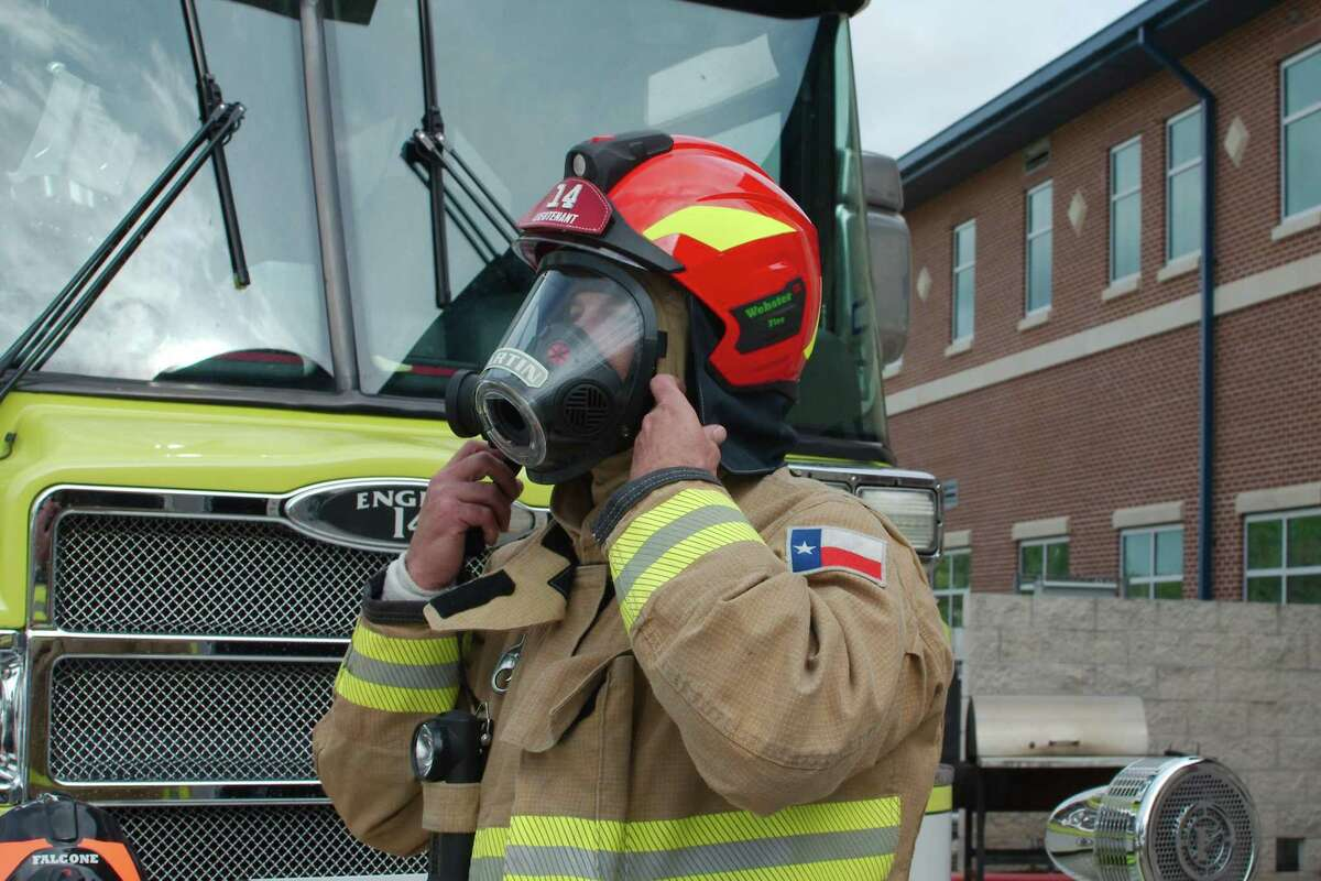 Webster firefighter Shane Martin straps the new-style fire helmet that his department is using.