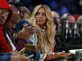 FILE - In this Feb. 19, 2017. file photo, Beyonce sits at court side during the second half of the NBA All-Star basketball game in New Orleans.  The pop star said on Thursday, April 4, 2019, she is on board as a creative partner for Adidas, and she will develop new footwear and apparel for the brand. Beyonce is also planning to re-launch her activewear clothing line, Ivy Park, with Adidas. (AP Photo/Max Becherer, File)