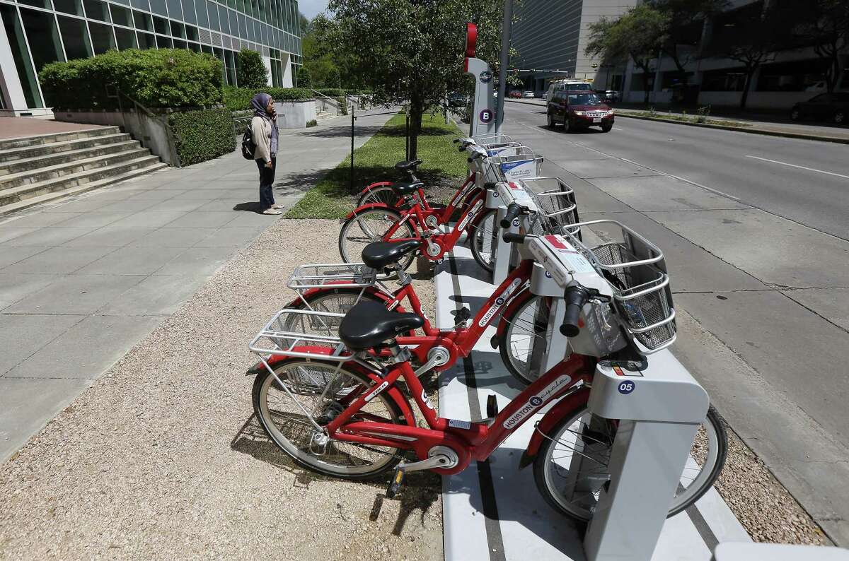 A woman makes a phone call before checking out a B-Cycle bike sharing system bike in the Texas Medical Center on April 2.