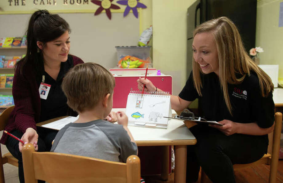 SIUE speech-language pathology graduate students Maren Valyo (left) and Hannah Greeling (right) lead a speech and language screening with a child at the Metro East Montessori School. Photo: For The Intelligencer
