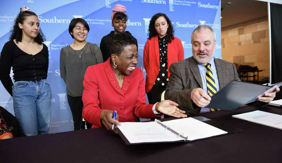 New Haven Superintendent of Schools Carol Birks, front left, and Southern Connecticut State University President Joe Bertolino, front right, sign an agreement between SCSU and New Haven Public Schools Thursday to offer tuition-free classes to students at their high school campuses. In the background are, from left, Sound School junior Clara Ortiz, Wilbur Cross High School junior Daniela Flores and senior Hannah Providence, and SCSU sophomore Dayana Lituma. Photo: Arnold Gold / Hearst Connecticut Media / New Haven Register