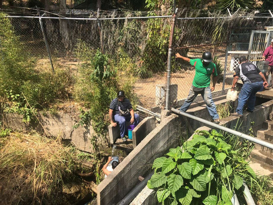 3ba1e768f People fill bottles with water from the Sabas Nieves creek in eastern  Caracas. Photo: