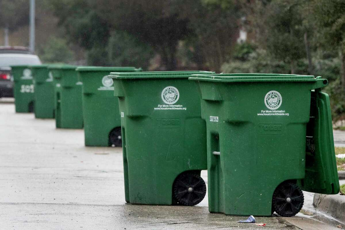 A line of recycling bin stands emptied along West Clay Street in January 2019. Under a proposal before city council, such bins would carry a monthly $0.57 charge; households in Houston with both city-provided garbage bins and recycling bins would be charged $1.14 per month.