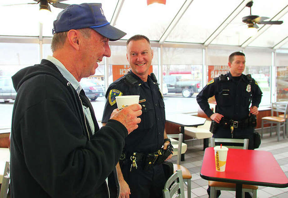 Everett Johnson (left) attends Coffee with a Cop on Wednesday at Hardee's so he could see his brother, Lt. Chris Johnson (center), and their nephew, Officer Alex Johnson (right). Jacksonville Police Department holds Coffee with a Cop events so Jacksonville residents can ask questions and get to know the department. Photo: Rosalind Essig | Journal-Courier