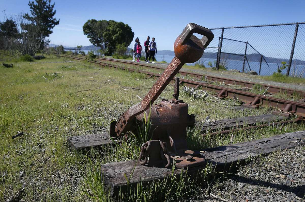 Jameisha Perkins and her daughter Janiyah Flowers, 10, walk with young friends past an old manual railroad switch on the perimeter of Miller/Knox Regional Shoreline in Richmond, Calif. on Saturday, March 30, 2019. The East Bay Regional Park District wants to remove some long abandoned sections of railroad tracks but the BNSF Railway Company wants to reactivate a portion of the spur.
