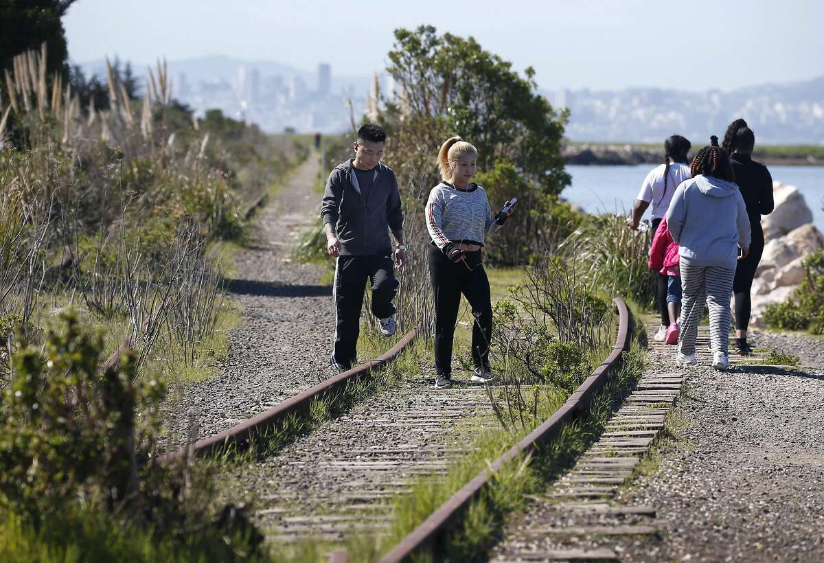 Jerry and Nai Saephan step across old railroad tracks on the perimeter of Miller/Knox Regional Shoreline in Richmond, Calif. on Saturday, March 30, 2019. The East Bay Regional Park District wants to remove some long abandoned sections of railroad tracks but the BNSF Railway Company wants to reactivate a portion of the spur.