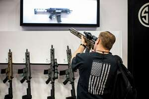 FILE -- A visitor checks out a rifle at a manufacturer's booth at the National Rifle Association's annual meeting in Dallas, May 5, 2018. Guns Down America, a gun control advocacy group, has graded big banks on their policies and practices related to the firearms industry. (Ashley Gilbertson/The New York Times)