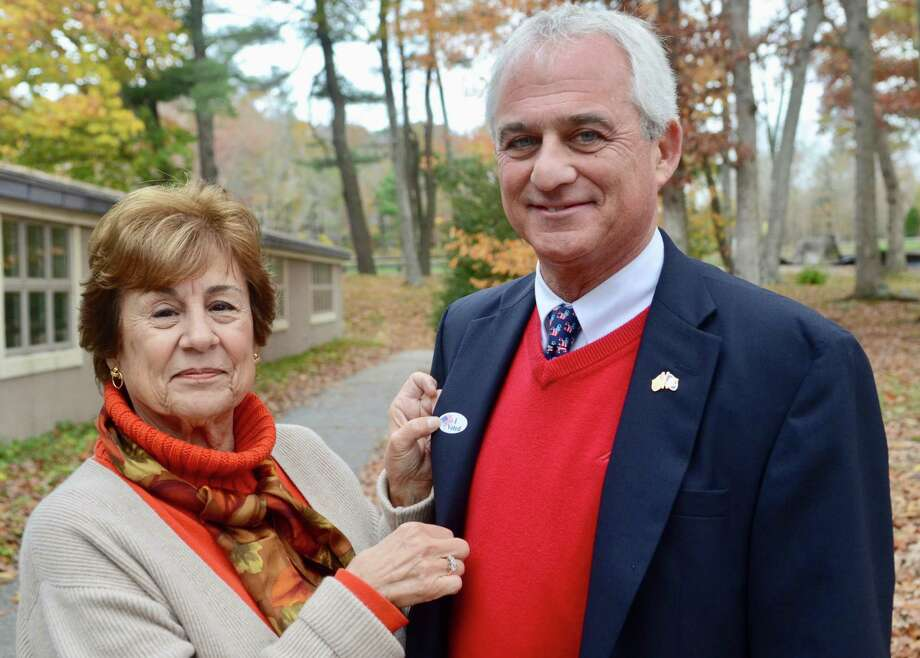 "Madison First Selectman Tom Banisch, right, is pictured on Election Day in November 2017, when he was elected to his second term. Donna Dougherty, a voter registration poll worker, puts an ""I Voted"" sticker onto his jacket. Photo: Kelly Goddard / Hearst Connecticut Media File"