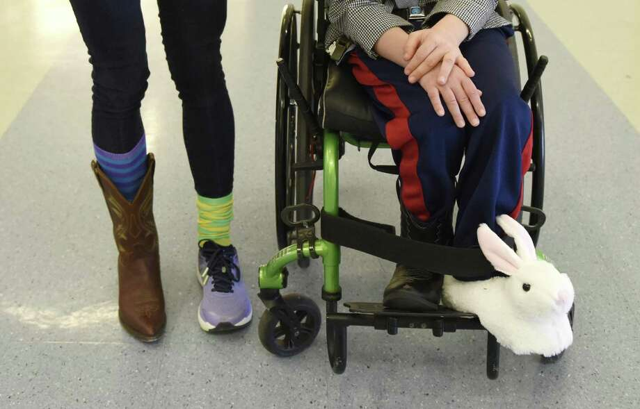 Glenville student Sam Buck, 8, wears mismatched shoes beside para-professional Lisa Gioffre at Glenville School in the Glenville Section of Greenwich, Conn. Thursday, April 4, 2019. Glenville student Sam Buck has Vanishing White Matter disease and many of his classmates and teachers showed support by wearing mismatched shoes and socks, something Buck is known for doing at school. The event raised money for the VWM Families Foundation, which supports families of those suffering from the genetic disorder that affects only about 250 kids in the world. Photo: Tyler Sizemore / Hearst Connecticut Media / Greenwich Time