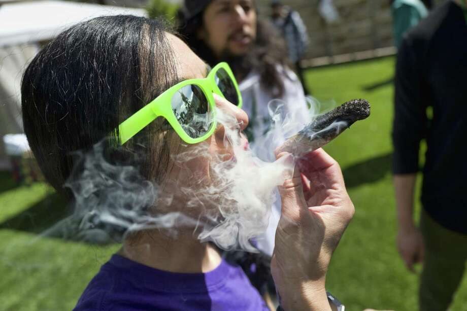 "FILE - In this Friday, March 22, 2019 file photo, a participant takes a very smoky puff from a marijuana cigarette during at meet and greet at ""Tommy Chong's Live, Love, and Smoke Tour hosted by GreenTours in the Woodland Hills section of Los Angeles. Los Angeles prosecutors are joining other California district attorneys to tap technology that could wipe out or reduce more than 50,000 old marijuana convictions. District Attorney Jackie Lacey announced Monday, April 1, 2019, that she is joining forces with a nonprofit organization that uses computer algorithms to identify eligible cases. San Francisco became the first city in the state to work with Code for America to expunge or reduce 8,000 convictions. (AP Photo/Richard Vogel, File) Photo: Richard Vogel, STF / Associated Press / Copyright 2019 The Associated Press. All rights reserved."