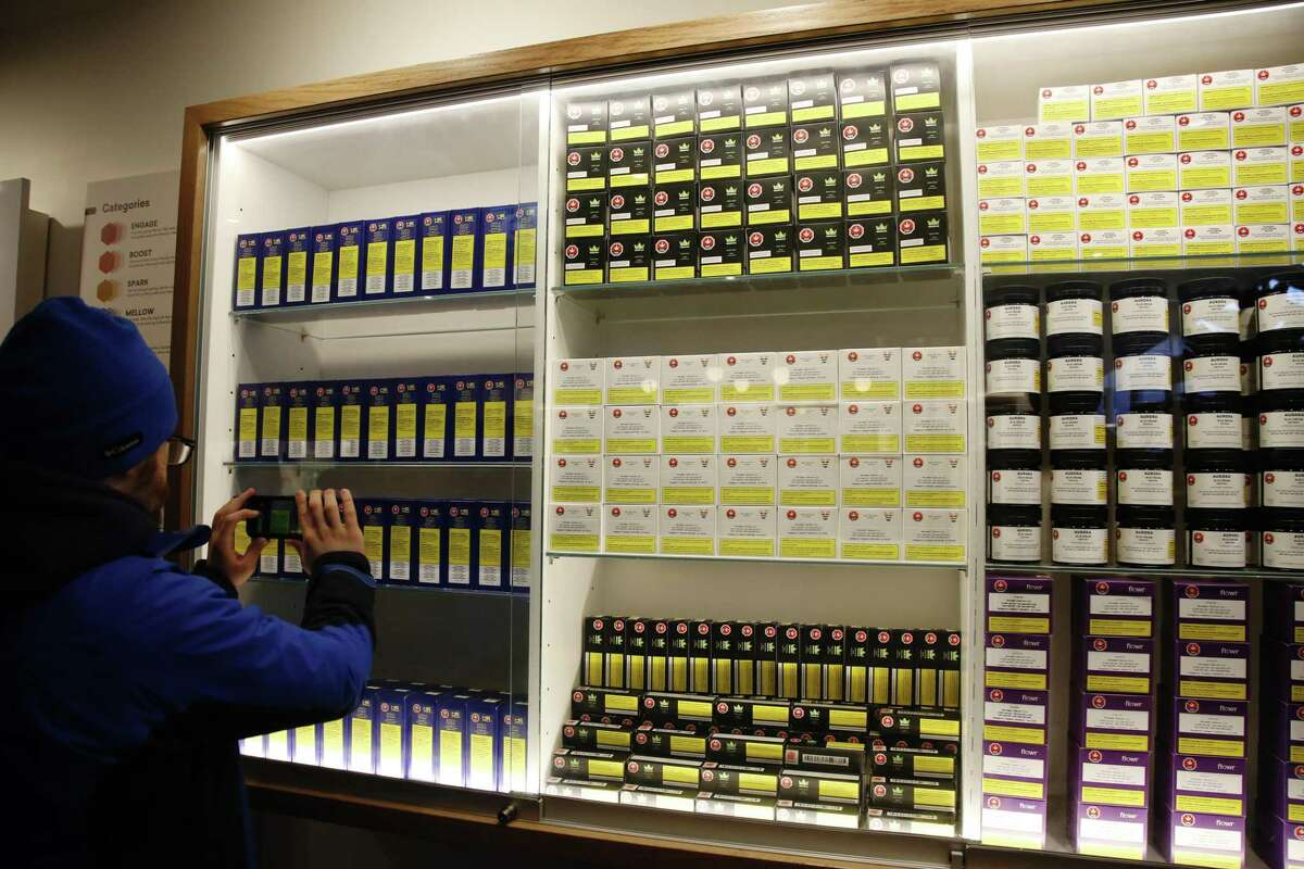 A customer takes a photo of cannabis products on display at the Fire & Flower cannabis shop in Ottawa, Ontario, Canada, on Monday, April 1, 2019. Canada's most populous province will finally open its first pot shops, nearly six months after legalization. Only 10 stores in Ontario had received the necessary licenses to open on April 1. Photographer: David Kawai/Bloomberg