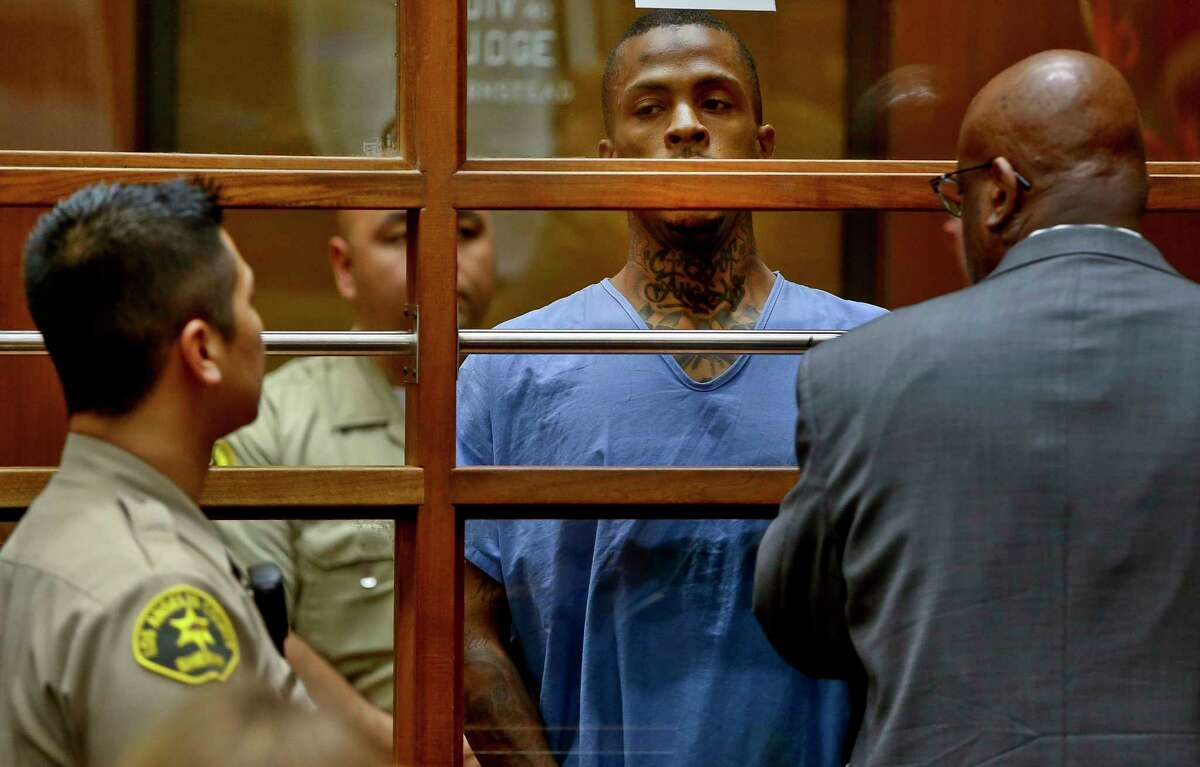 Eric Holder, center, the suspect in the killing of rapper Nipsey Hussle is seen with his attorney, Christopher Darden, front, in Los Angeles County Superior court Thursday, April 4, 2019. Holder, 29, is charged with murder and two counts of attempted murder in connection with the attack outside Hussle's The Marathon clothing store on Sunday.