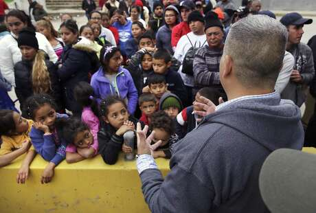 Michael Benavides, of Team Brownsville, explains to an unexpectly large crowd that he may not have enough food to feed everyone at a make-shift camp at the international bridge in Matamoros on Tuesday, April 2, 2019. Bendavides and other volunteers take meals across every morning and evening.