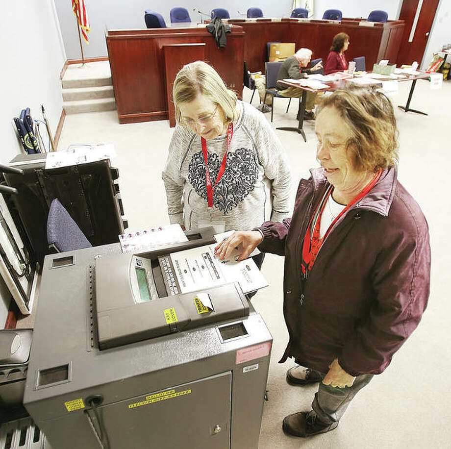 Election Judge Lillian Phipps, left, watches as fellow judge Bonnie McClain, of Wood River, feeds her ballot into the tabulation machine Tuesday morning at Wood River Precinct 3, which voted at Wood River City Hall. McClain took advantage of the peace and quiet to cast her vote while waiting. By 9 a.m. only five people had cast ballots in the precinct.