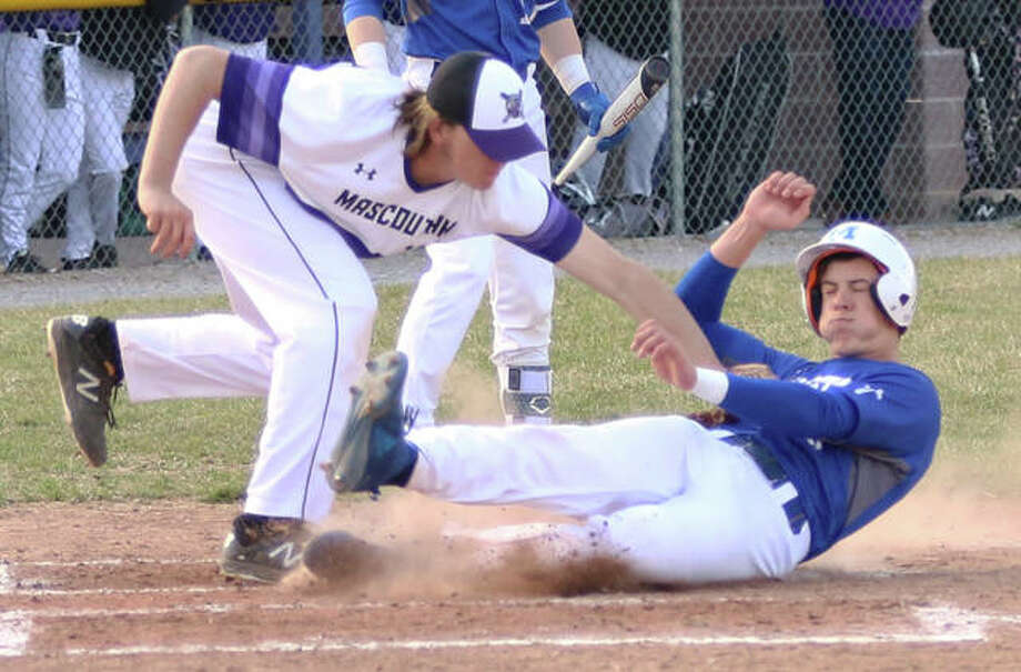 Marquette Catholic's Garrett Weiner (right) gets to the plate ahead of the tag from Mascoutah pitcher Jack Owens to score from second base on a wild pitch for the Explorers' lone run in a 12-1 loss Wednesday at Mascoutah. Photo: Greg Shashack / The Telegraph