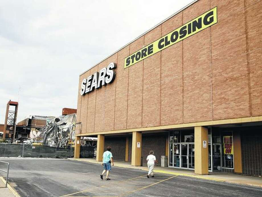 People walk into a Sears store that was slated for closing in July 2017 in Overland Park, Kansas. Sears is working on recovering from bankruptcy by opening smaller stores with no clothing and a focus on appliances, mattresses and home services. One of the new stores will be in Overland Park. Photo: Charlie Riedel | Associated Press