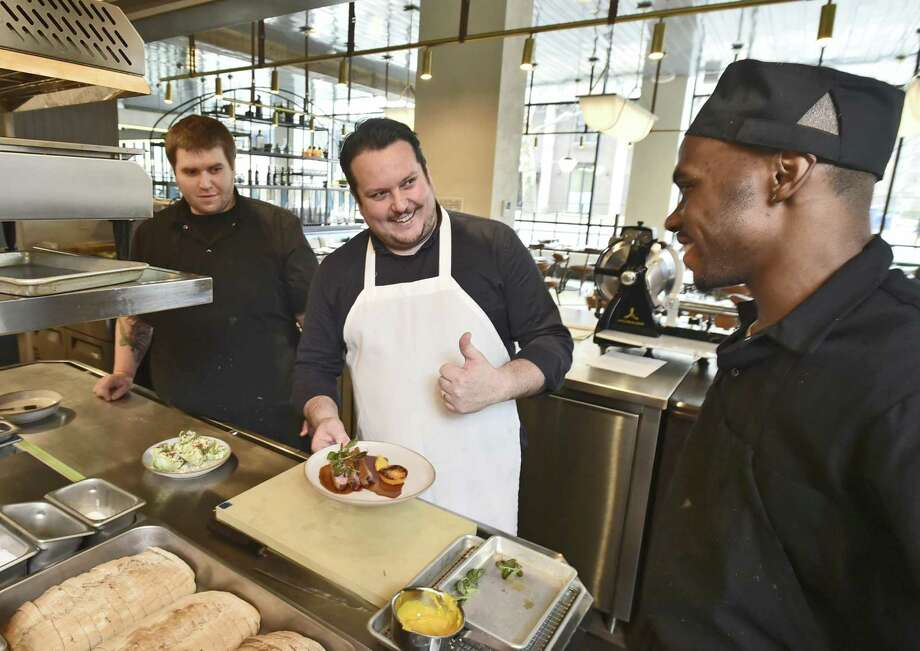 New Haven, Connecticut - Friday, March 29, 2019: Chef Matt Lambert, center, shows off his Duck l'orange with satsuma, confit satsuma, satsuma puree with cress with with sous chefs Cory Pastore, left, and Jahquari Greene, right, in the open kitchen at the Hamilton Park restaurant in The Blake hotel on High Street in New Haven. Photo: Peter Hvizdak / Hearst Connecticut Media / New Haven Register