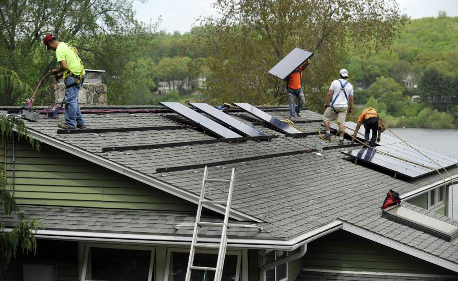 A crew with Danbury, Conn.-based Ross Solar Group at work in May 2015 in nearby Brookfield. Photo: Carol Kaliff / Carol Kaliff / The News-Times