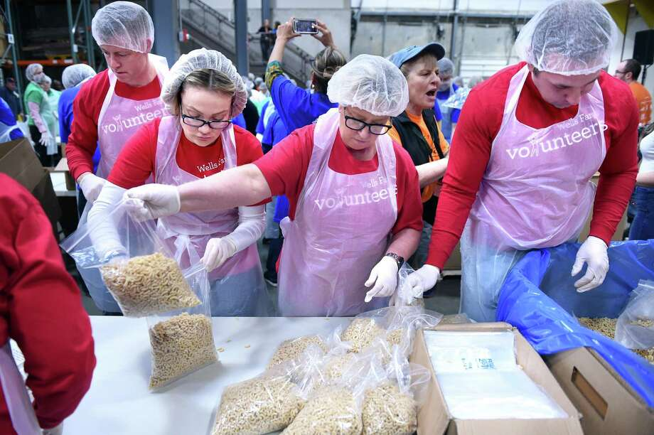 Employees of Wells Fargo bag elbow macaroni during the third annual Golden Scoop Championship at the Connecticut Food Bank in Wallingford April 4.Nine teams from different companies scooped, bagged, labeled, sealed and packed boxes of 30,000 pounds of elbow macaroni in the competition. Stop & Shop placed first. Ocean State Job Lot placed second and Wells Fargo placed third. Photo: Arnold Gold / Hearst Connecticut Media / New Haven Register