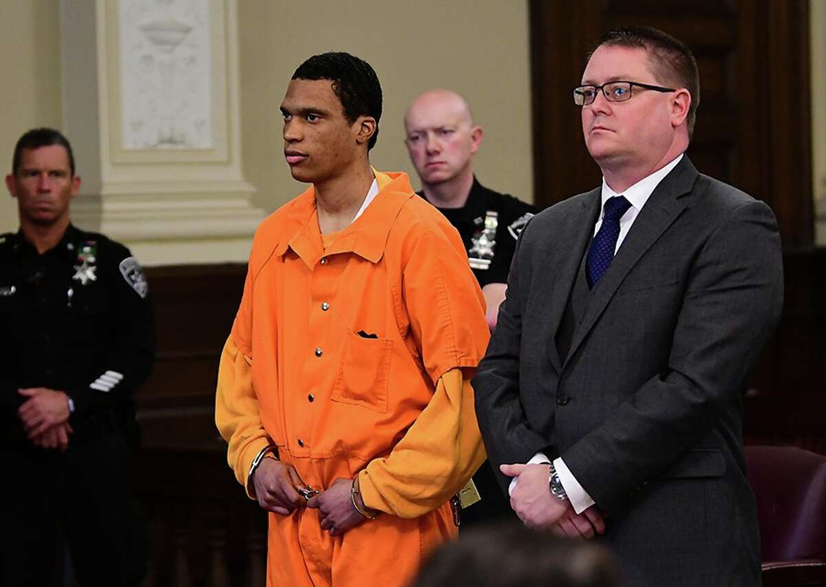 Justin Mann, 25, left, and his attorney, Joseph Ahearn, stand in Rensselaer County Court Friday. Mann pleaded guilty to second-degree murder in the killings of two women and two children in Troy two years ago as part of a plea deal that he requires him to testify at the upcoming trial of another man charged in the case.