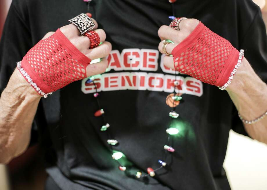 Sandy Hallmark, 73, adjusts her necklace before the Space City Seniors performance at the Toyota Center. Hallmark has been on the dance team for 10 years. Photo: Elizabeth Conley/Staff Photographer