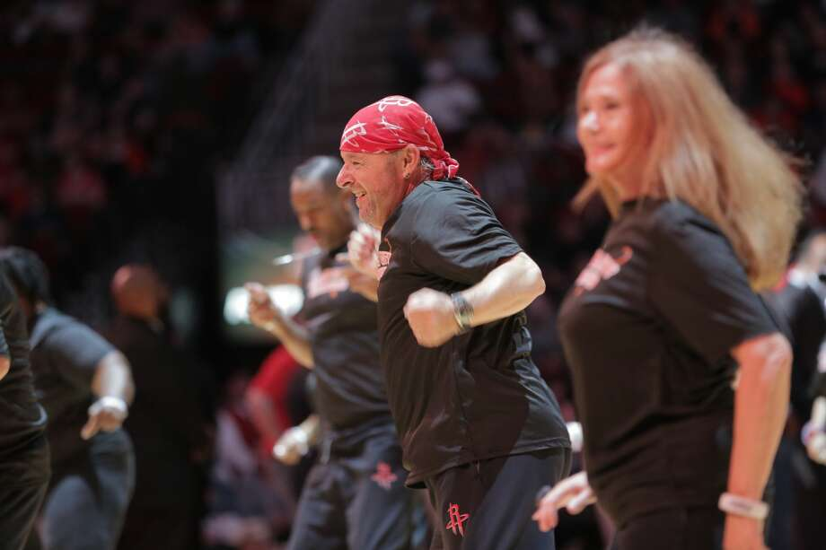 "Michael Sweigart smiles as he performs with the Space City Seniors during a timeout at the Houston Rockets and Portland Trailblazers game. ""When people start reacting to you, the roar, there's nothing like it,"" said Sweigart. Photo: Elizabeth Conley/Staff Photographer"