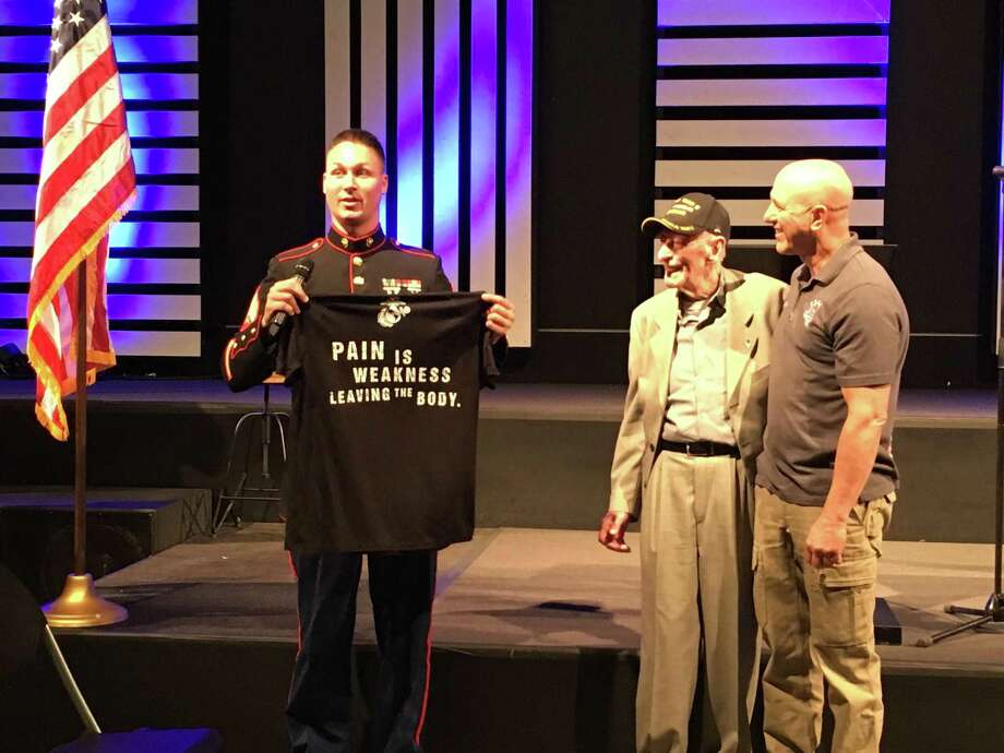 Marine Sgt. Zachary Head presented a T-shirt to World War II veteran Joseph Colwell at the March 31 Texans Embracing America's Military event. On the right is Ralph Oliver, T.E.A.M. founder. Photo: Karen Zurawski / Karen Zurawski