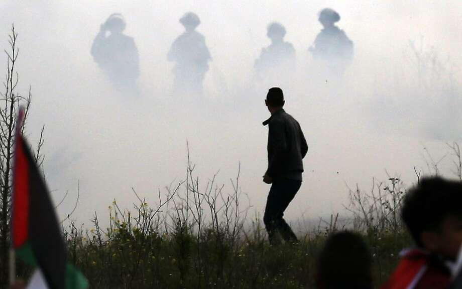 A Palestinian demonstrator is seen with Israeli security forces through the mist in the background, during clashes following a demonstration to plant olive trees in the village of Bizzariya, northwest of Nablus in the occupied West Bank, on March 29, 2019. (Photo by JAAFAR ASHTIYEH / AFP)JAAFAR ASHTIYEH/AFP/Getty Images Photo: JAAFAR ASHTIYEH / AFP/Getty Images / AFP or licensors