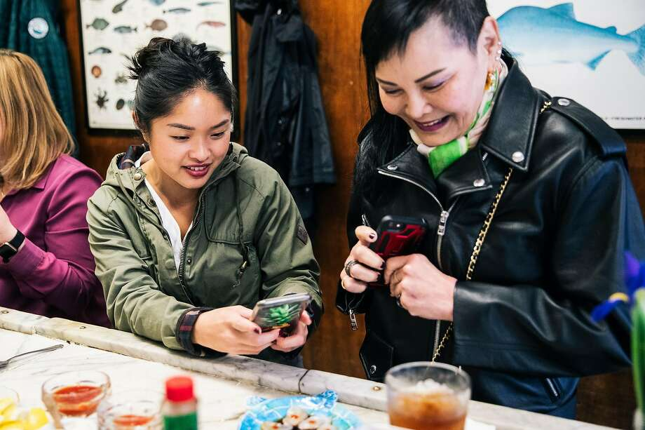 May Wong (left) and Meng Ong photograph a small version of the Dozen Eggs — sliced raw scallops in ponzu with Sriracha. Photo: Stephen Lam / Special To The Chronicle