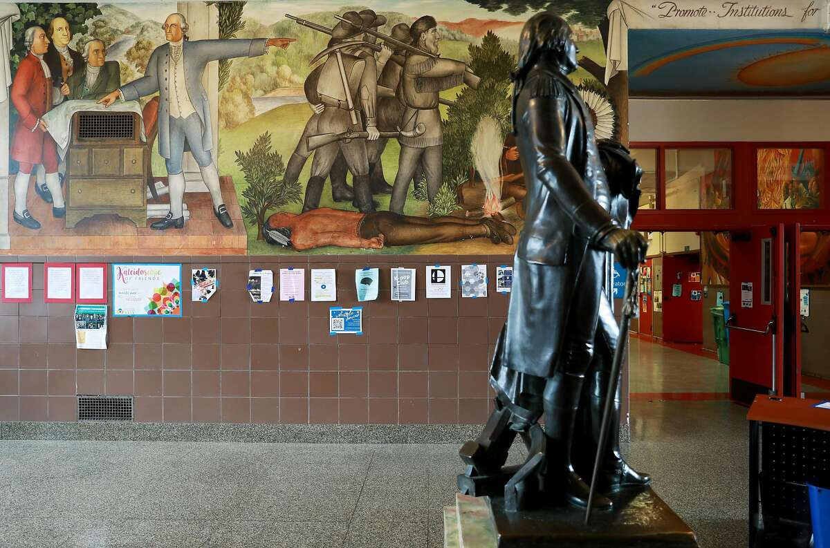 A statue of George Washington stands near a historic mural that depicts the treatment of American Indians and African Americans. San Francisco school officials are expected to decide whether to destroy or keep the historic mural at George Washington High School, photographed in San Francisco, Calif., on Wednesday, April 3, 2019.