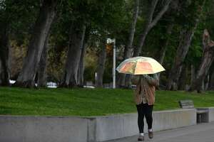 A woman stays dry under an iridescent umbrella as another rainstorm passes over the South Beach Harbor in San Francisco, Calif. on Friday, April 5, 2019.