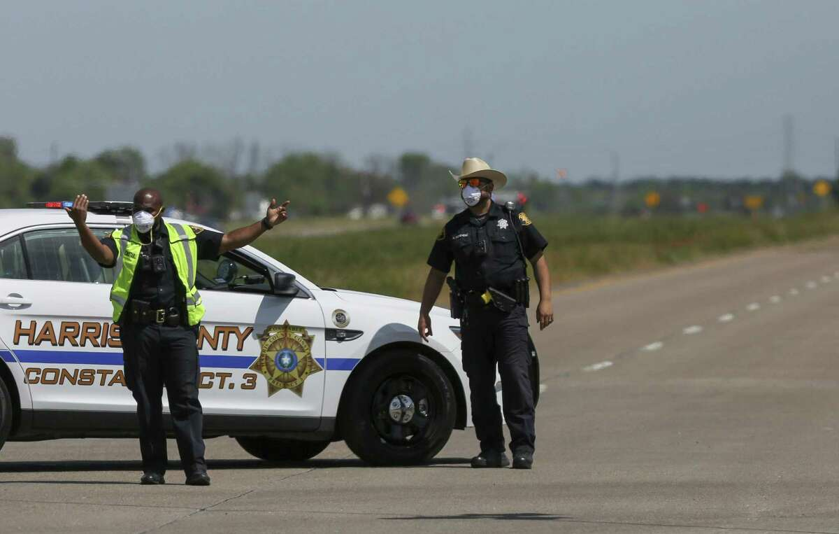 Harris County Constable Precinct 3 deputies direct traffic away from closed roads as firefighters battled a chemical fire at the KMCO plant Tuesday, April 2, 2019, in Crosby, Texas. A shelter-in-place was ordered for people living within one-mile radius of the plant. (Godofredo A. Vasquez/Houston Chronicle via AP)