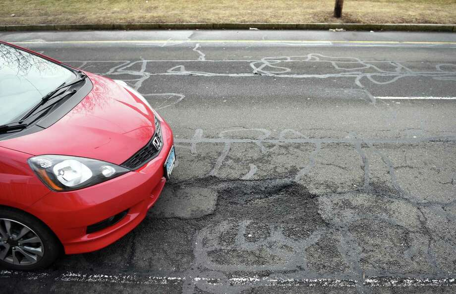 A car tries to avoid a pothole on North Frontage Road between Dwight and Orchard streets in New Haven on March 15. Photo: Arnold Gold / Hearst Connecticut Media / New Haven Register