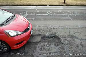 A car tries to avoid a pothole on North Frontage Road between Dwight and Orchard streets in New Haven on March 15.