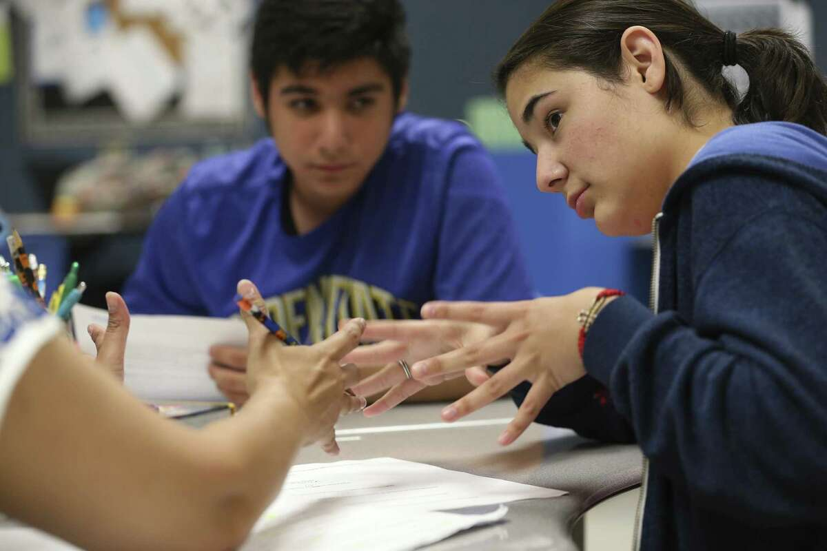 Liliana Garcia, 15, from Somerset ISD, discusses an lecture with Special Education teacher Evangelina Gantt during an English class at South San Antonio High School, Thursday, May 18, 2017. The South San Antonio ISD program for the deaf and hard of hearing is the hub for a dozen school districts in the southern region. In back is Jaime De La Garza, 18, from Harlandale ISD.