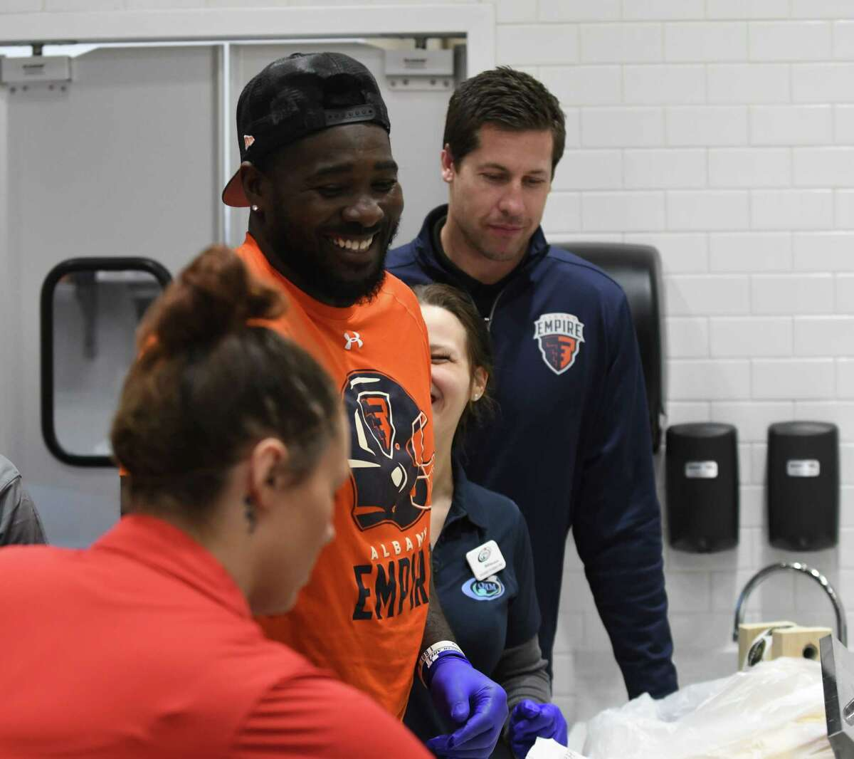 Albany Empire players Joe Sykes, center, and Tommy Grady, right, from the Albany Empire Arena Football League team, make sandwiches at the new Empire Deli at Albany International Airport on Friday, April 5, 2019, in Colonie, N.Y. The deli is located near the security gate on the unsecured side. It is branded in conjunction with the arena football team. (Will Waldron/Times Union)