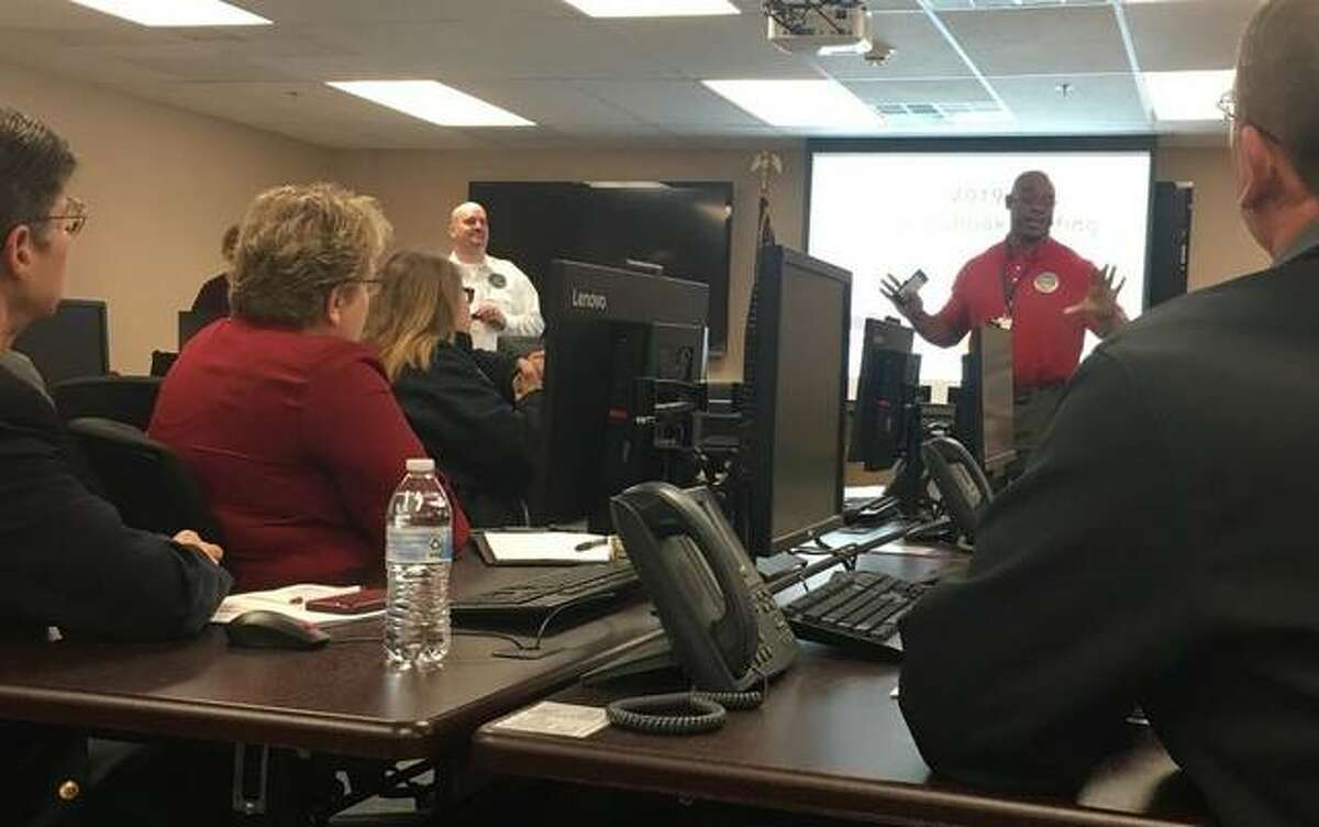 Madison County Emergency Management Agency Director Todd Fulton, standing center, and EMA Logistic Coordinator Tony Falconio, welcomed dozens of fire department, law enforcement, sanitary sewer and levee district, public works, county and elected officials, to a flood outlook briefing this week in Wood River.