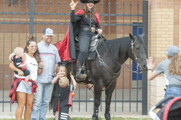Texas Tech fans and supporters get a picture with the Masked Rider 04/05/19 before the annual football scrimmage at Grande Communications Stadium. Tim Fischer/Reporter-Telegram