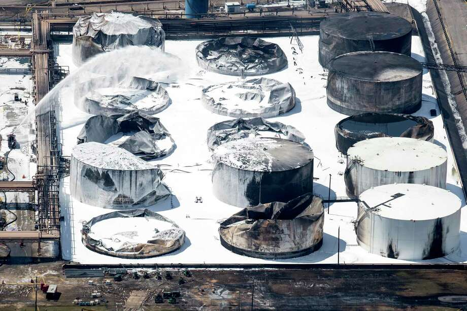 """Emergency crews continue to douse what's left of the now-extinguished petrochemical tank fire at Intercontinental Terminals Company on Wednesday, March 20, 2019, in Deer Park. Fire crews extinguished the blaze at ITC about 3 a.m., Wednesday, almost four days after it started, which caused a plume of black smoke to linger over the Houston area. ITC officials said the cause of the fire is still unknown. EPA on-site coordinator Adam Adams said they have been in Deer Park since Sunday, conducting air monitoring at ground level and in the plume. Biggest concerns are """"volatile organic chemicals"""" and particulates, Adams said. He added that no hazardous levels have been detected. Photo: Brett Coomer, Houston Chronicle / Staff Photographer / © 2019 Houston Chronicle"""