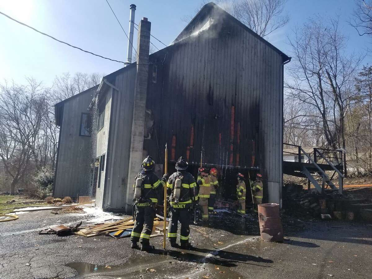 Danbury firefighters assist New Fairfield and Sherman firefighters at the 117 Route 39 house fire on April 4, 2019.