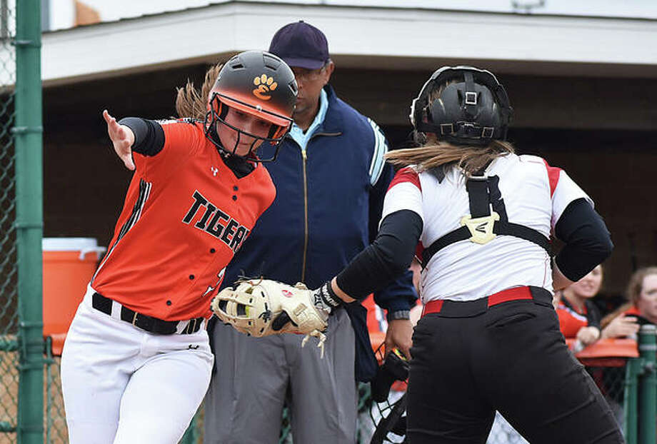 Edwardsville's Mackenzie Owens, left, tries to avoid the tag at the plate during the second inning. She was called out on the play.