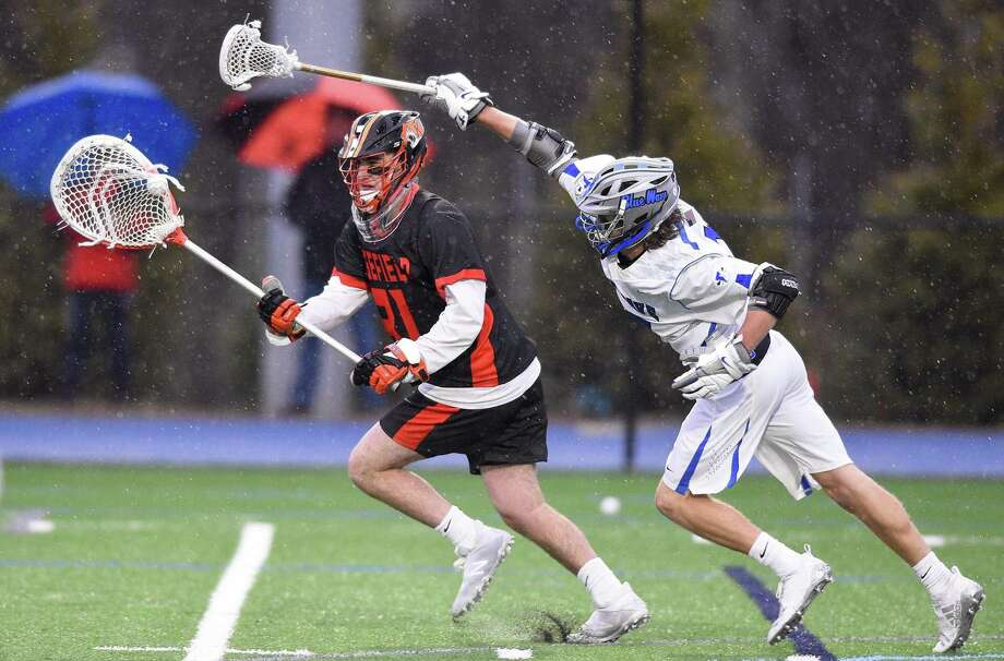 Ridgefield goalie Dan Parson (31) evades Darien's Henri Pfeifle (15) in the first period of a boys lacrosse match at Darien High School on Friday in Darien. Darien defeated Ridgefield 14-6. Photo: Matthew Brown / Hearst Connecticut Media / Stamford Advocate