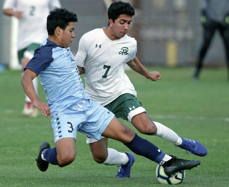 Johnson's Justin Jaramillo, left, sneaks in to tackle the Rattler's Isaiah Mcalanis as Reagan plays Johnson in boys soccer at Blossom Soccer Stadium on April 5, 2019. Photo: Tom Reel, Staff / Staff Photographer / 2019 SAN ANTONIO EXPRESS-NEWS